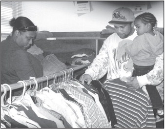 The Yates family - Desharrah, Frank and Simira - browse through the J.O. Combs Unified School District Food Bank's clothing selection, where they found some tops and pants for little Simira.