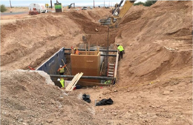 Construction crews work to install a manhole on the fourth phase of the Hunt Highway Improvement Project.